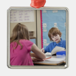 Girl (10-11) and boy (6-7) reading in classroom metal ornament