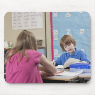 Girl (10-11) and boy (6-7) reading in classroom mouse pad