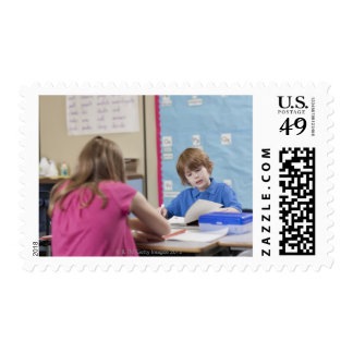Girl (10-11) and boy (6-7) reading in classroom postage stamp