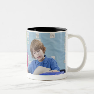 Girl (10-11) and boy (6-7) reading in classroom Two-Tone coffee mug
