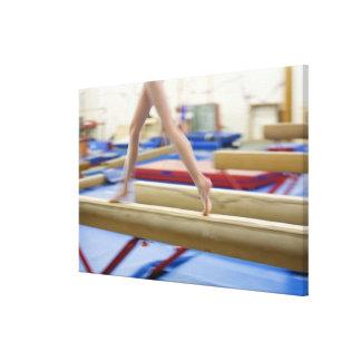 Girl (16-17) running on balance beam, low canvas print