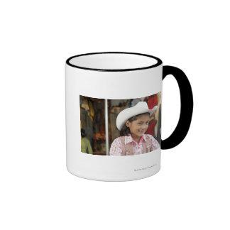 Girl (8-10) wearing stetson, smiling ringer coffee mug