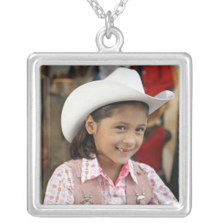 Girl (8-10) wearing stetson, smiling silver plated necklace