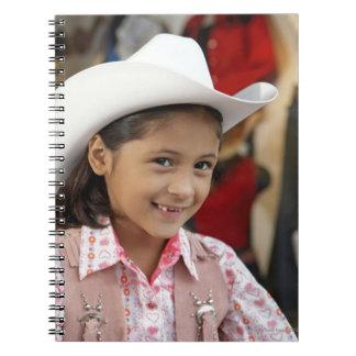Girl (8-10) wearing stetson, smiling spiral notebook