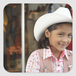 Girl (8-10) wearing stetson, smiling square sticker