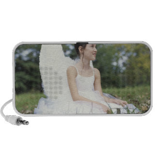 Girl (9-11) sitting on grass wearing angel notebook speakers
