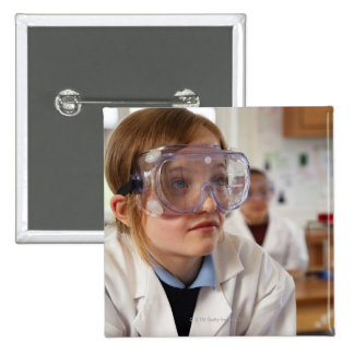 Girl (9-12) wearing protective goggles in button