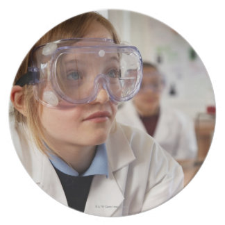 Girl (9-12) wearing protective goggles in dinner plate