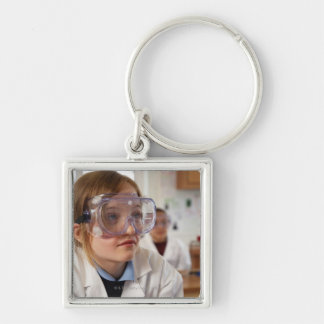 Girl (9-12) wearing protective goggles in Silver-Colored square keychain