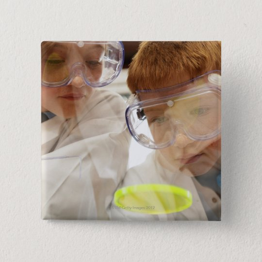 Girl and boy (11-13) looking at petri dish, view pinback button