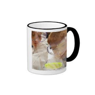 Girl and boy (11-13) looking at petri dish, view ringer mug