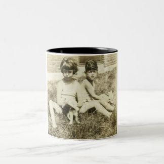 Girl and boy with cats on grass mug