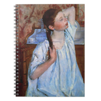 girl arranging her hair spiral note book