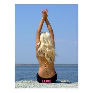 girl-blonde sits on coast postcard