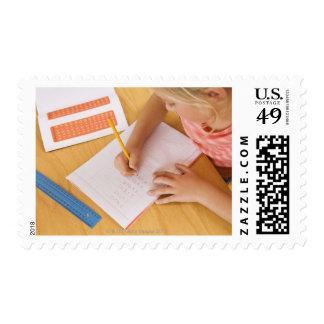 Girl doing homework postage stamps