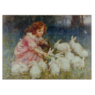 Girl feeding rabbits cutting board