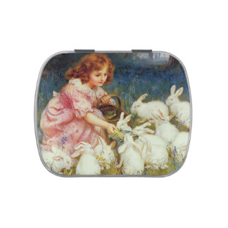 Girl feeding white rabbits candy tins
