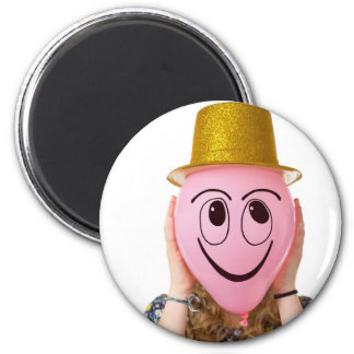 Girl holding balloon with smiling face and hat magnet