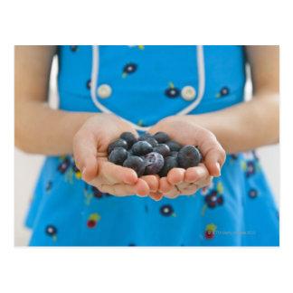 Girl holding fresh blueberries postcard