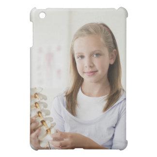 Girl holding model of spine in doctors office iPad mini case