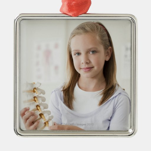 Girl holding model of spine in doctors office square metal christmas ornament