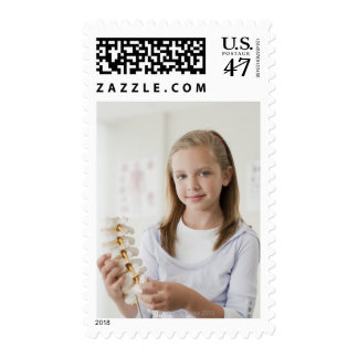 Girl holding model of spine in doctors office postage
