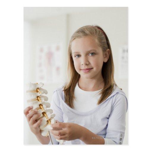 Girl holding model of spine in doctors office postcards