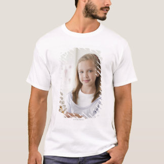 Girl holding model of spine in doctors office T-Shirt