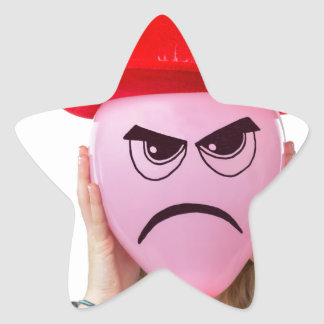 Girl holding pink balloon with angry face and hat star sticker