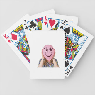 Girl holding pink balloon with smiling face bicycle playing cards