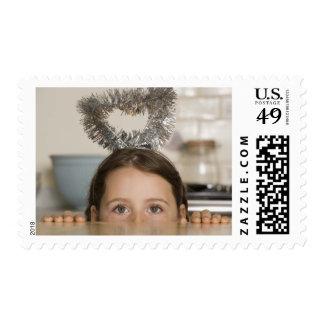 Girl in angel costume peeking from behind postage