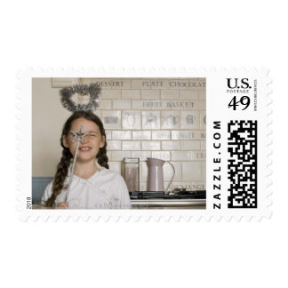 Girl in angel costume playing with wand postage stamps