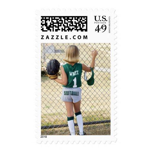 Girl in softball uniform postage