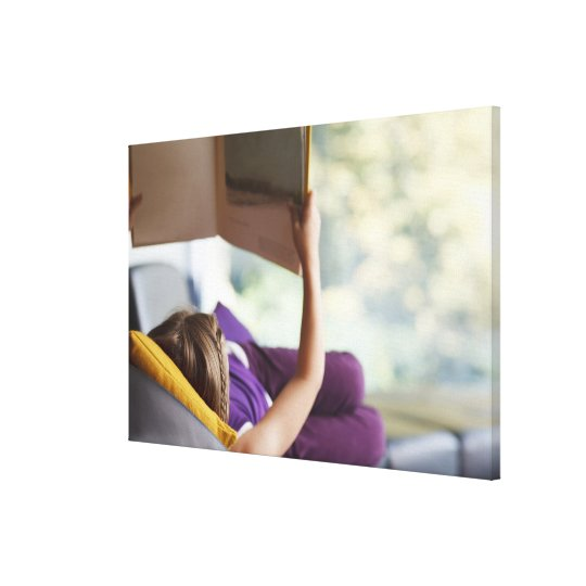 Girl laying down reading book canvas print