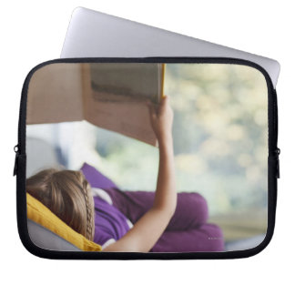 Girl laying down reading book laptop sleeve