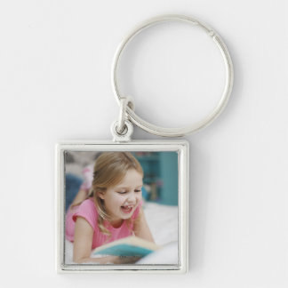 Girl laying in bed reading book keychain