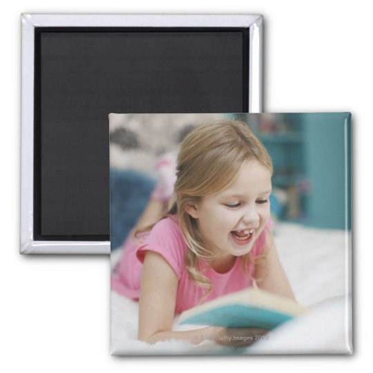 Girl laying in bed reading book magnet