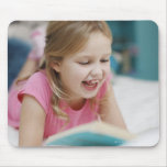 Girl laying in bed reading book mouse pad