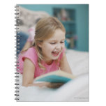 Girl laying in bed reading book notebook