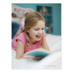 Girl laying in bed reading book postcard
