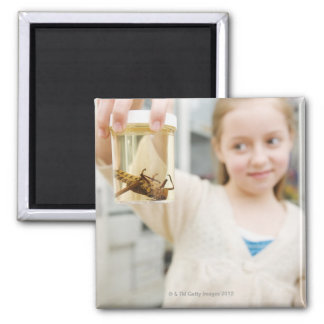 Girl looking at insect in jar in classroom 2 inch square magnet