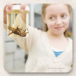Girl looking at insect in jar in classroom drink coaster