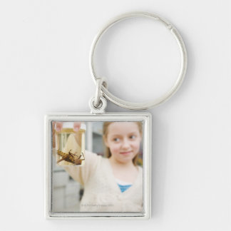 Girl looking at insect in jar in classroom keychain