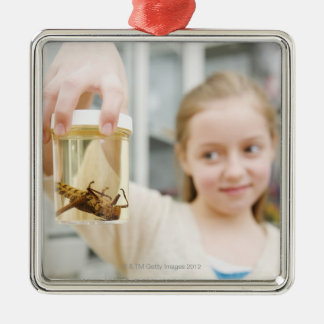 Girl looking at insect in jar in classroom metal ornament