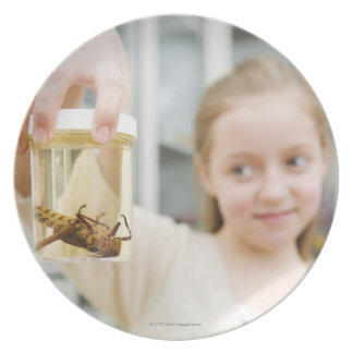 Girl looking at insect in jar in classroom plate