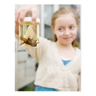 Girl looking at insect in jar in classroom postcard