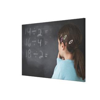 Girl looking at math equations on blackboard canvas print