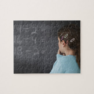 Girl looking at math equations on blackboard jigsaw puzzle