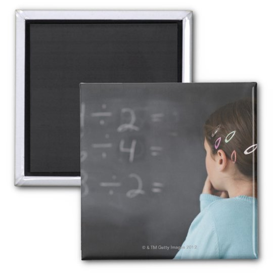 Girl looking at math equations on blackboard magnet