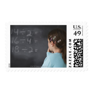 Girl looking at math equations on blackboard postage